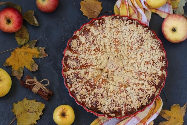 Пирог с яблоками расположен в керамической форме на темном фоне, вид сверху, крупный план, ориентация горизонтальная.