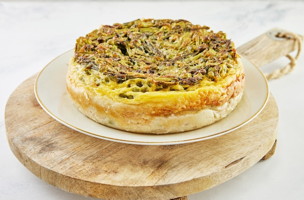 プレートと木製のスタンドにアスパラガスとエンドウ豆のパイ。ステップバイステップのレシピ。