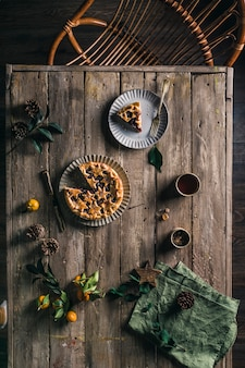 Pie with berries on a wooden table with a serving top view.