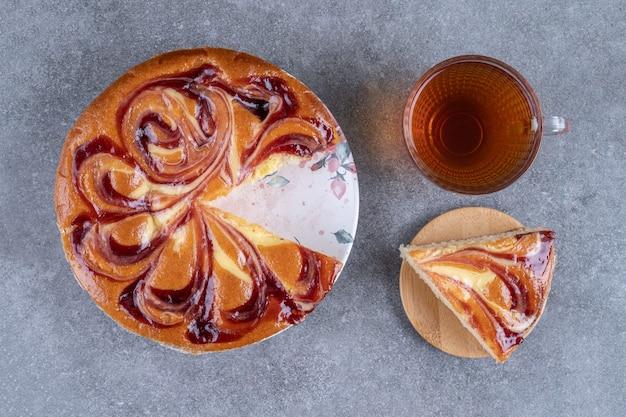 Torta con frutti di bosco e tazza di tè su superficie di marmo