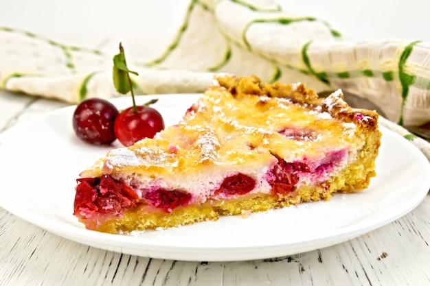 접시에 체리와 사워 크림 파이, 나무 판의 배경에 수건