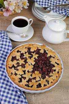 Pie with cherry filling decorated flowers and petals