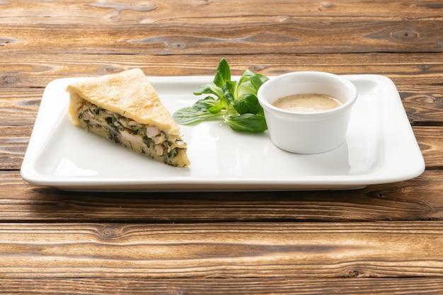 Пирог с курицей и зеленью в белой керамической тарелке
