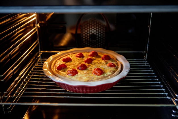 Pie with chicken and tomatoes is on a baking sheet in the oven. quiche loren