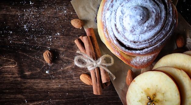 나무 테이블에 계피와 사과 파이. 호두와 설탕 가루를 곁들인 계피 스틱을 곁들인 신선한 페이스트리. 테이블에 견과류와 계피를 넣은 롤빵.