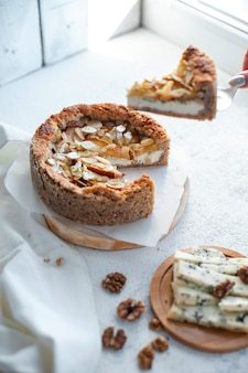 Dor 블루 치즈, 배, 아몬드 파이, 흰색 테이블에 접시에 전체 라운드.