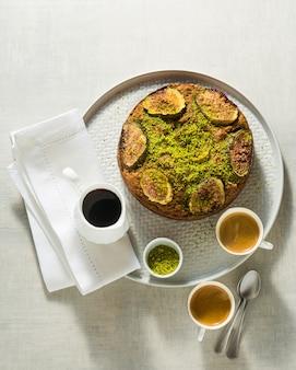 Пирог с инжиром и фисташками на столе с чашками кофе эспрессо и кленовым сиропом. утренний завтрак или летний бранч