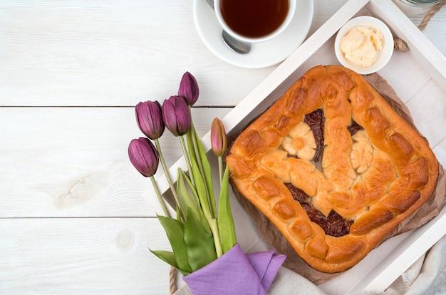 Пирог с фруктовой начинкой и букетом тюльпанов на светлом фоне. вид сверху с пространством для копирования.
