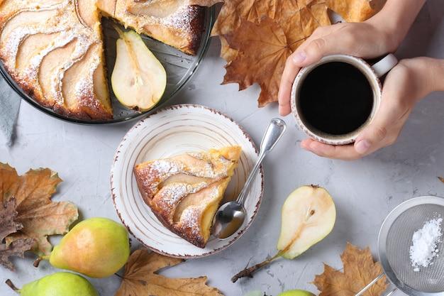 梨、女性の手でコーヒー、灰色の背景に紅葉、上からの眺めとパイ