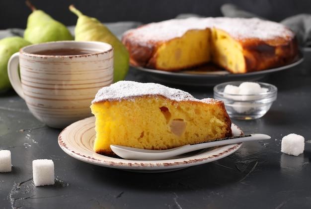 暗い背景にカットピースとお茶のカップと梨とパイ。