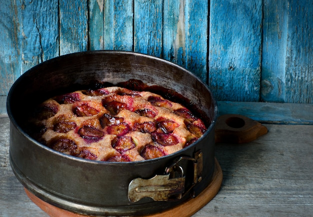 Pie with plums in a metal baking dish