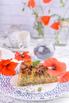 Pie with poppy seeds on a white background. homemade pastries and red flowers