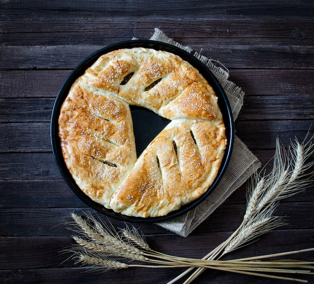 Pie with sesame on a sacking and ears of wheat. dark wooden background, top view