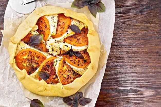 위에서부터 나무 판자 배경에 있는 양피지에 토마토, 커드 치즈, 보라색 바질을 넣은 파이