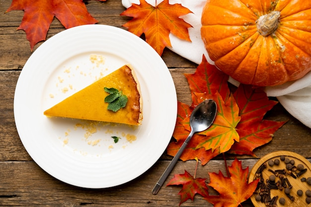 A piece of american pumpkin pie on a white plate and a wooden table, autumn flatly.