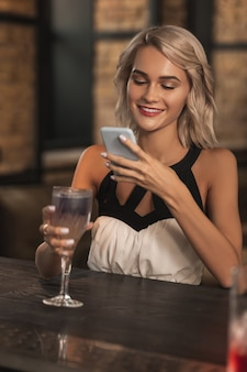 Piece of art. beautiful blonde woman sitting at the bar counter and taking a photo of her cocktail while smiling
