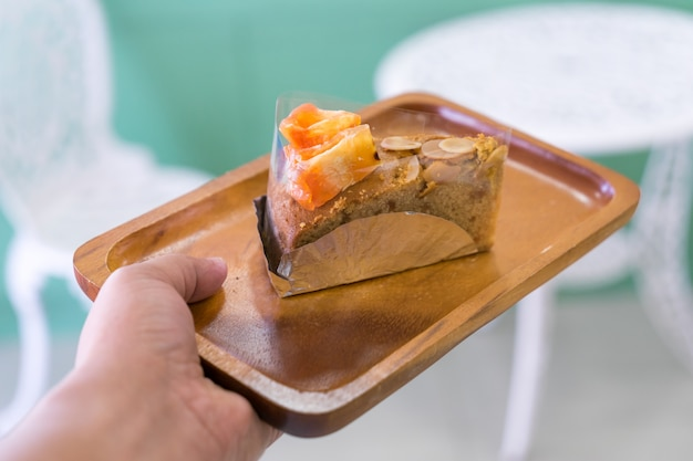 Piece of bael fruit cake on wood plate on hand