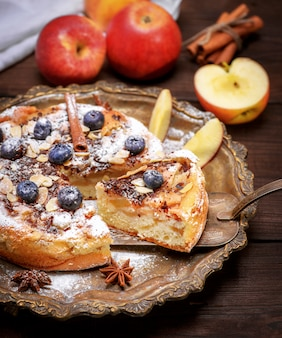 Piece of baked pie with apples on an iron spatula