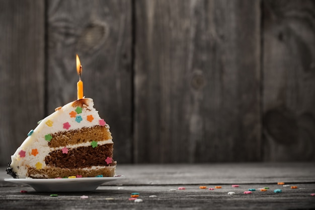 Piece of birthday cake on wooden background
