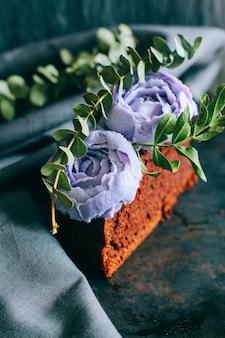 Piece of birthday chocolate cake with purple cream roses