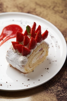 A piece of biscuit roll with cream and strawberry. cake roll with fresh strawberries on white plate. luxury restaurant dessert