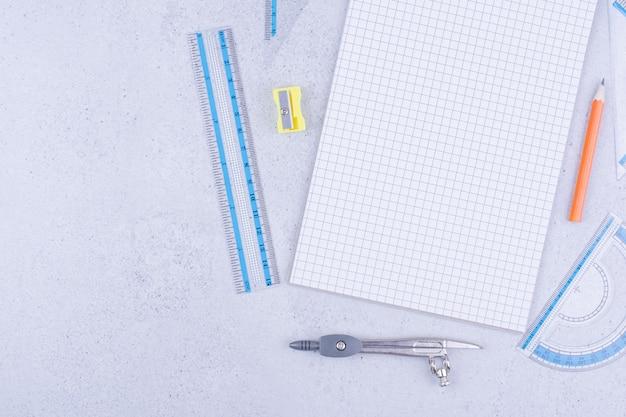 Un pezzo di carta bianca con penna, matita carboncino, righello e divisori intorno