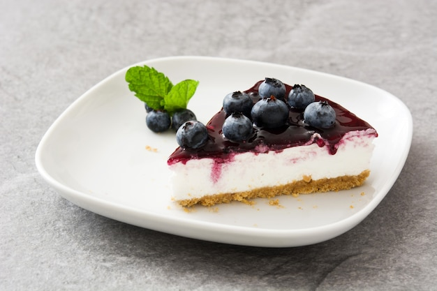Piece of blueberry cheesecake on gray stone