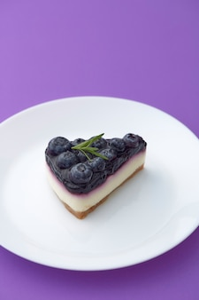 Piece of blueberry cheesecake on white plate on violet background