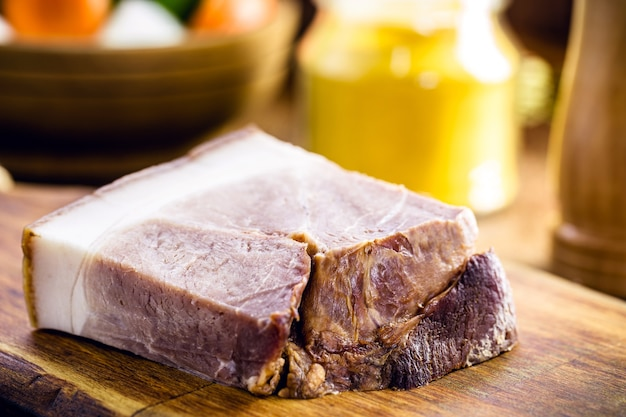 Piece of brazilian bacon cut on a meat board, culinary ingredient