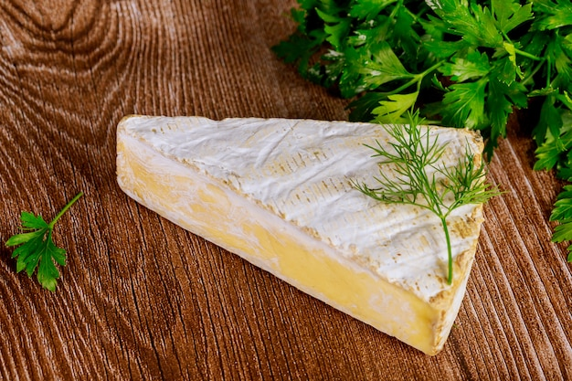 Piece of brie creme cheese on wooden surface