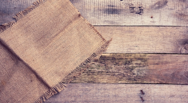Piece of burlap with torn edges on a surface of gray wooden boards, top view