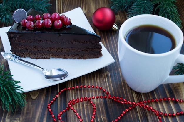 Piece of cake, coffee and christmas composition on the wooden background