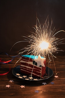 Piece of cake in the colors of the usa flag with sparklers on a dark background, independence day celebration, 4th of july concept, close up.