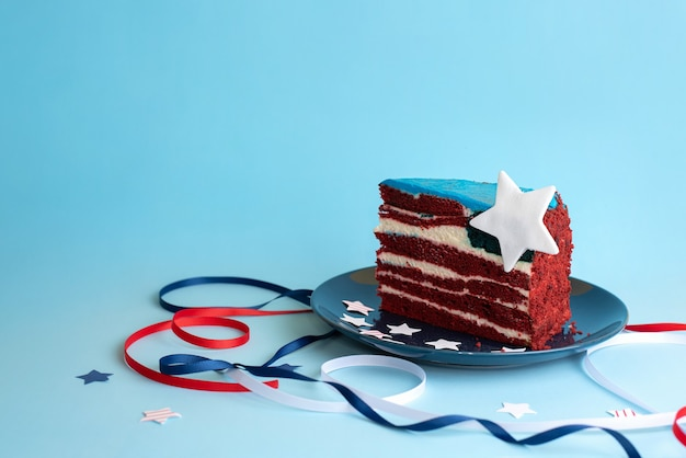 A piece of cake in the form of the usa flag with white, red and blue ribbons and stars on a blue background, celebrating independence day, close up.
