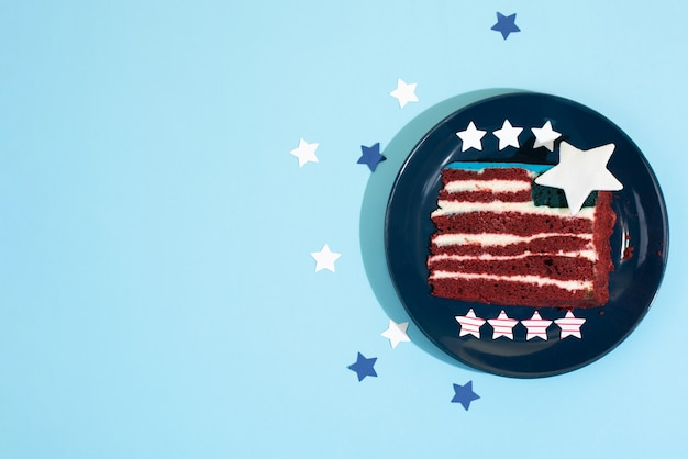 A piece of cake like the usa flag on a plate with stars on a blue background, food for the party for independence day, close up.