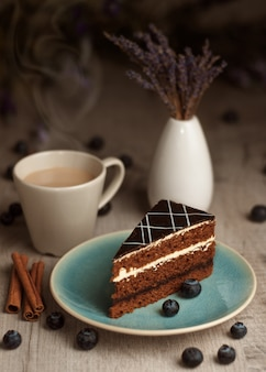 A piece of cake on a plate and a cup of coffee.