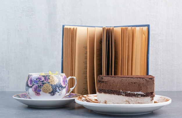 A piece of cake with aroma tea and book.