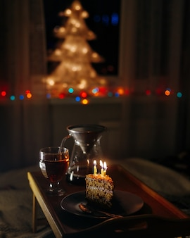 A piece of cake with burning candles in a dark room birthday or holiday greeting a surprise