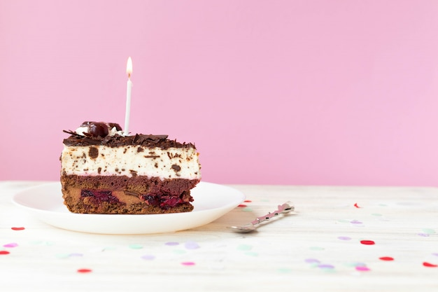 A piece of cake with a candle, a tart for a birthday, space for text
