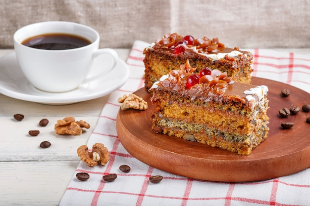 A piece of cake with caramel cream and poppy seeds on a wooden kitchen board and a cup of coffee, white table.