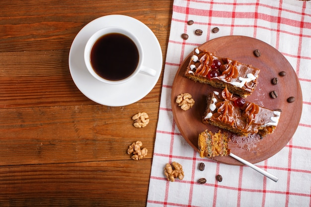 A piece of cake with caramel cream  on a wooden kitchen board and a cup of coffee