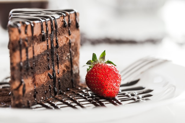 Piece of cake with chocolate creame and fork isolated on white