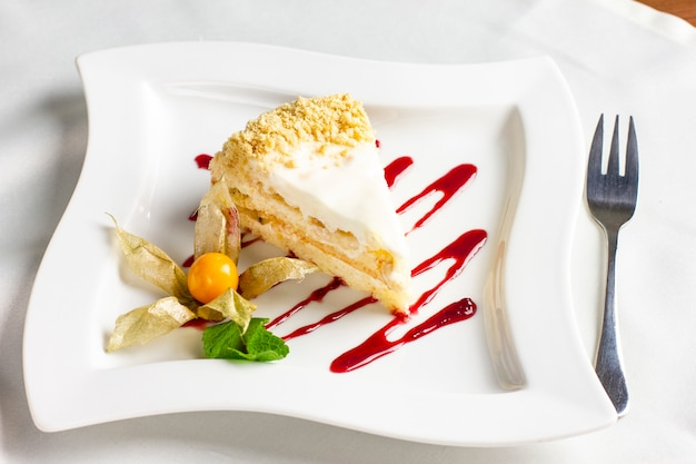 The piece of cake with cream and physalis on white plate