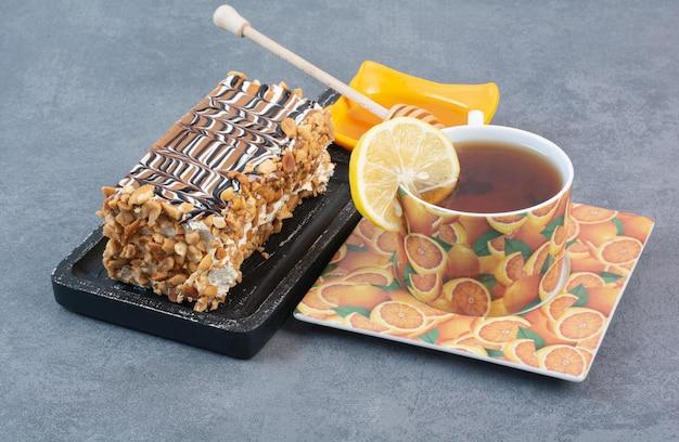 Un pezzo di torta con una tazza di caffè aromatizzato sulla superficie grigia