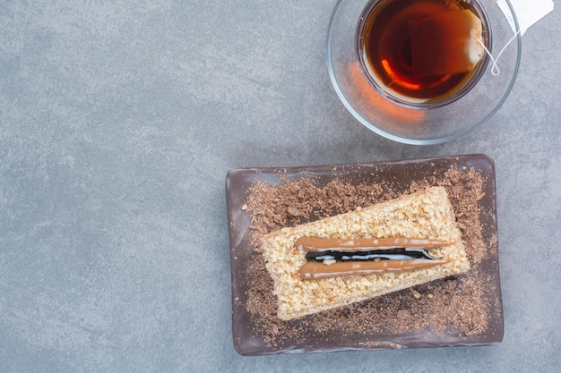 A piece of cake with cup of aroma coffee on gray surface