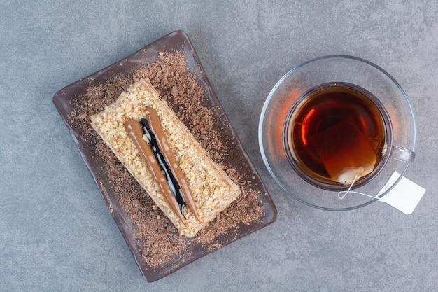 Un pezzo di torta con una tazza di caffè aromatizzato sul tavolo grigio.