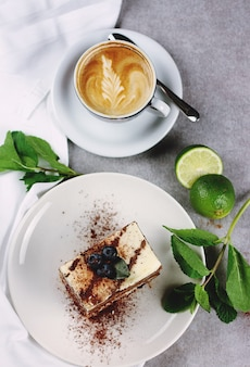 A piece of cake with a cup of cappuccino, a slice of lime and twigs of mint