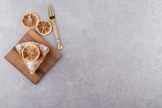 A piece of cake with fork and dried slices of lemon placed on stone table.