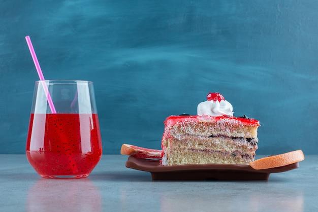 Un pezzo di torta con una tazza di vetro di succo rosso.