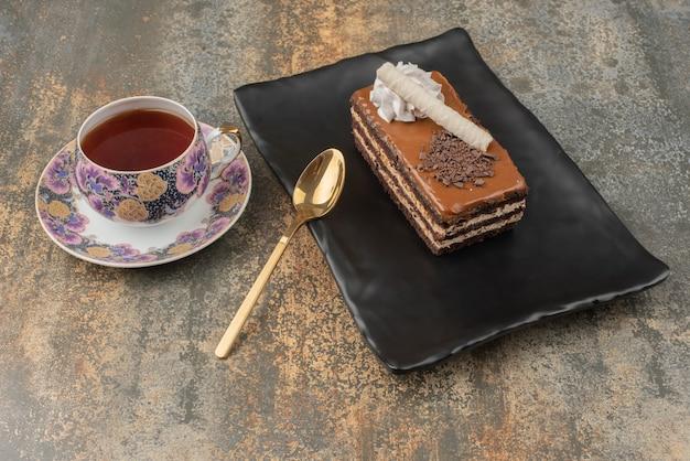 Un pezzo di torta con tè caldo e cucchiaio sul piatto scuro